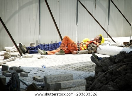 SHANGHAI, CHINA - MAY 2, 2015: Chinese construction worker resting under the sun, near the Hangpu River in Pudong. Shanghai is one of the fastest growing cities in the world.  - stock photo