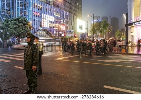 SHANGHAI, CHINA - MAY 2, 2015: Policeman on duty making sure the traffic flows at Nanjing Road. It is the main shopping street of Shanghai, China, and is one of the world's busiest shopping streets. - stock photo