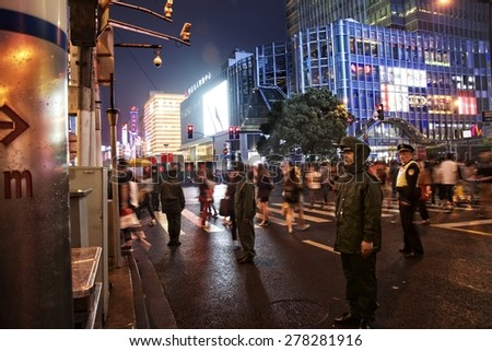 SHANGHAI, CHINA - MAY 2, 2015: Visitors and neon lights at Nanjing Road. It is the main shopping street of Shanghai, China, and is one of the world's busiest shopping streets. - stock photo