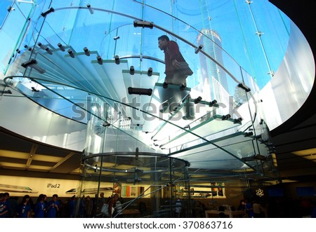 Shanghai, China - October 18, 2011: Visitor is walking up the spiral staircase located inside the Apple Store in Shanghai. This store opened in 2010         - stock photo