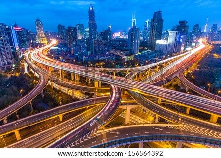 SHANGHAI - CIRCA APRIL 2013 - Night skyline view of city and highways with flowing traffic, circa April 2013 - stock photo