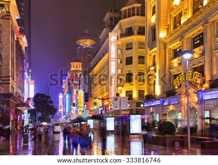 SHANGHAI, CN - OCT 31, 2014: Architecture of Nanjing Road - the main shopping street of Shanghai, China at night after rain  - stock photo
