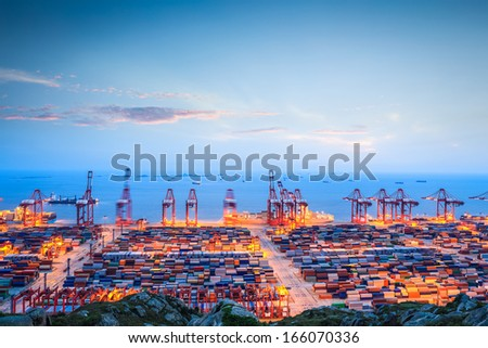 shanghai container terminal in twilight ablaze with lights  - stock photo