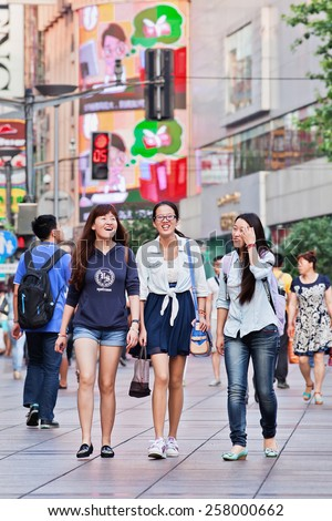 SHANGHAI-JULY 5, 2014. Cheerful young women in shopping area. Lives of women in China have significantly changed after government made efforts towards gender equality in a male-dominated society.  - stock photo