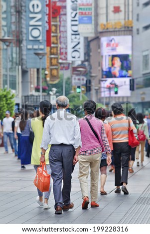 SHANGHAI-JUNE 4, 2014. Group of Chinese people walk in Nanjing East Street. It is Shanghai's main shopping street, named after the city Nanjing, and one of the world's busiest shopping streets.  - stock photo