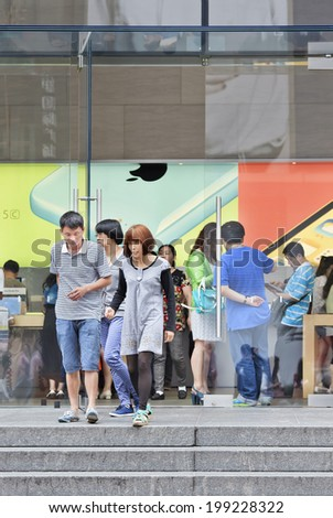 SHANGHAI-JUNE 4, 2014. People walk out the Shanghai Apple flag-store. According Umeng, China's largest analytic firm, 27% of China's smartphones cost over  $500, and 80% of those are i Phones. - stock photo