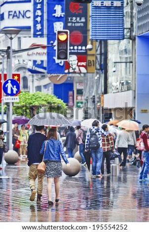 SHANGHAI-MAY 4, 2014. Shoppers with umbrella in wet Nanjing East Road. Shanghai has a humid subtropical climate, its summer is very warm and humid, with occasional downpours or freak thunderstorms.   - stock photo