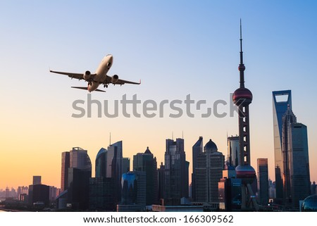 shanghai modern buildings skyline with airplane in sunrise  - stock photo