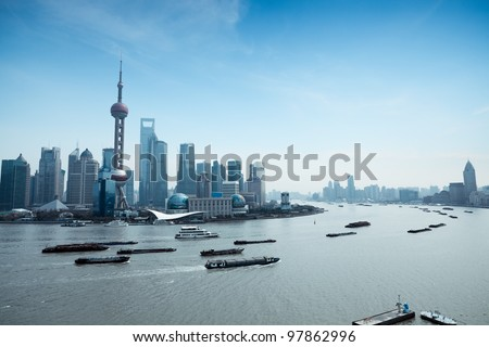 shanghai pudong skyline and busy huangpu river - stock photo