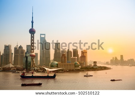 shanghai skyline and huangpu river at dusk - stock photo