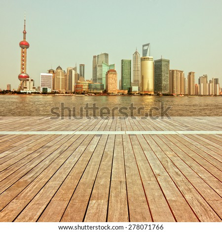 shanghai skyline in afternoon and reflection with wooden floor - stock photo