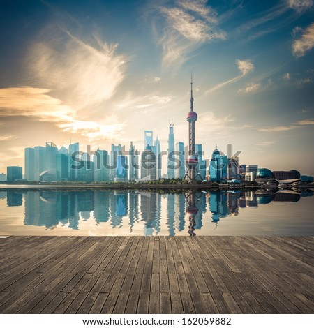 shanghai skyline with reflection and wooden floor in sunrise  - stock photo