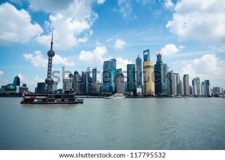 shanghai skyline with sightseeing cruise at daytime - stock photo