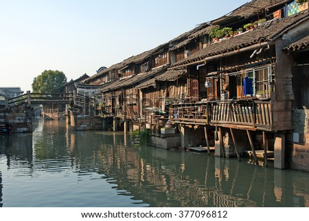 Shanghai, Wuzhen historic scenic town old houses and bridge reflection in a canal.   - stock photo