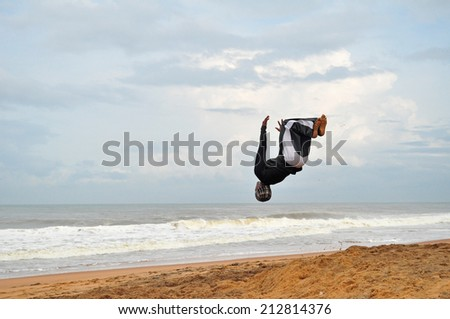SHANGHUMUGHAM, TRIVANDRUM, KERALA, INDIA, CIRCA NOVEMBER 2013: Acrobat performing cartwheel on the beach in the early morning