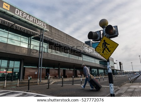 Shannon airport, Ireland - November 21st  2016: A man with luggage walks across the crosswalk towards the flight departures area of Shannon airport.