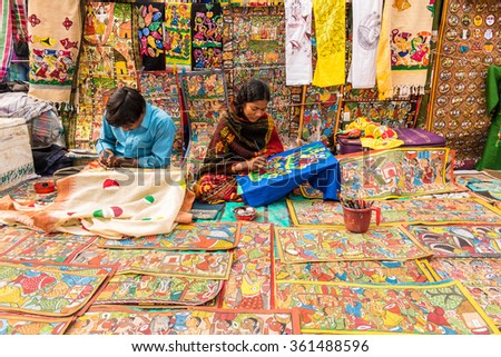 SHANTINIKETAN, INDIA - DECEMBER 25: An Indian artist couple paints colorful handicraft items for sale during the annual Poush Mela fair 2015 on December 25, 2015 in Shantiniketan, West Bengal, India. - stock photo