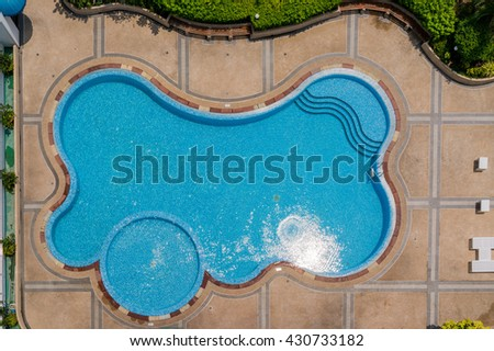 Shape and curves of big blue swimming pool with green garden. - stock photo