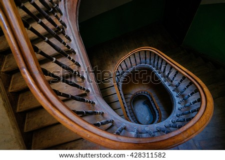 Shape, architecture and perspective. Beautiful old wooden spiral staircase. - stock photo