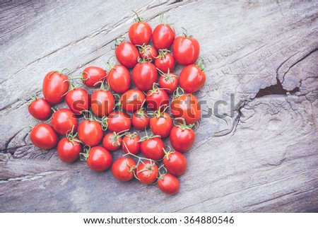 shape heart of tomatoes on old wooden table background - stock photo