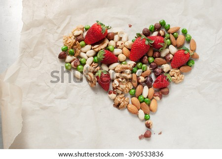 Shape Heart Strawberry Pea Peanut Almond Walnut Hazel Nut Paper Background Top view Healthy Concept - stock photo