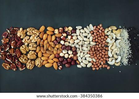 Shape Line Peanut Almond Cashew Walnut Hazel Nut Pecan Sesame Black Wooden Background Top view Healthy Concept - stock photo