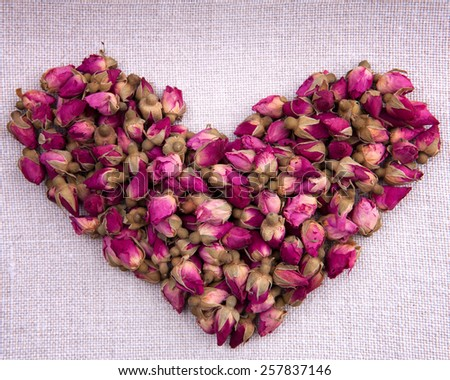 Shape of a heart made out of dried pink roses on fabric background - stock photo