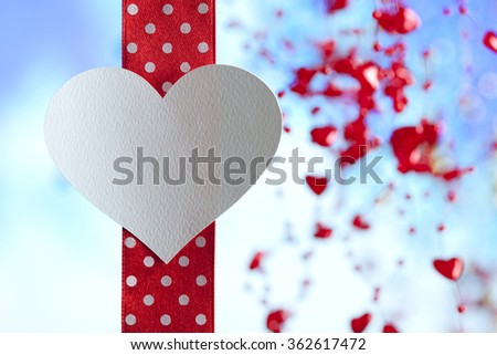 Shape of heart on red ribbon and blue background