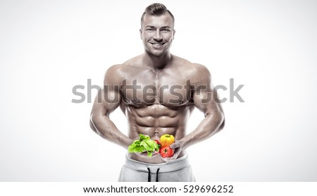 Shaped and healthy bodybuilder holding a fresh vegetables, shaped abdominal, isolated on white background, colored retouched