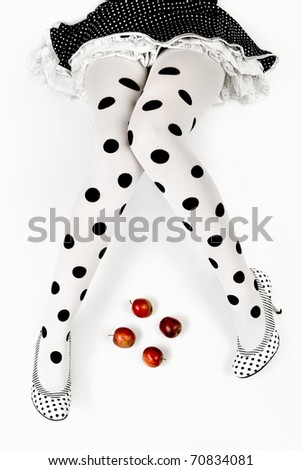 shaped legs, dotted tights, and four apples - conceptual - stock photo