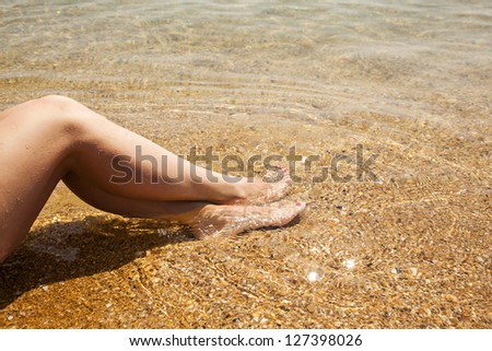 shapely female legs close-up on the beach in the water - stock photo