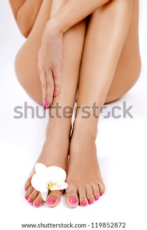 Shapely woman's legs with an orchid flower between toes - stock photo