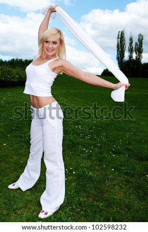 Shapely young smiling woman exercising and stretching outdoors on green grass in a fitness concept - stock photo