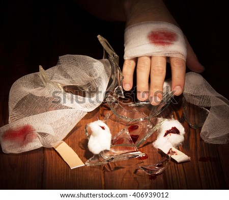 Shards glass injured and bandaged hand against the dark wood. - stock photo