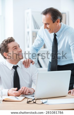 Sharing good experience. Cheerful businessman sitting at his working place while his chief touching his shoulder and standing near  - stock photo