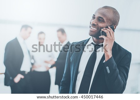 Sharing good news. Cheerful young African man in formalwear talking on the mobile phone and smiling while his colleagues standing on background - stock photo