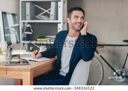 Sharing good news. Handsome young man talking on the mobile phone and looking over shoulder with smile while sitting at his working place in office - stock photo