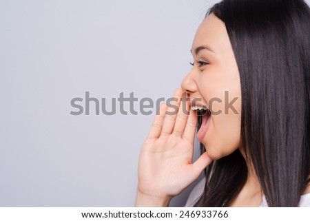 Sharing good news. Side view of beautiful young Asian woman shouting and holding hand near mouth while standing against grey background - stock photo