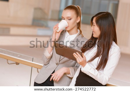 Sharing ideas. Young businesswoman sharing her ideas with her colleague drinking coffee during the coffee break at the meeting - stock photo
