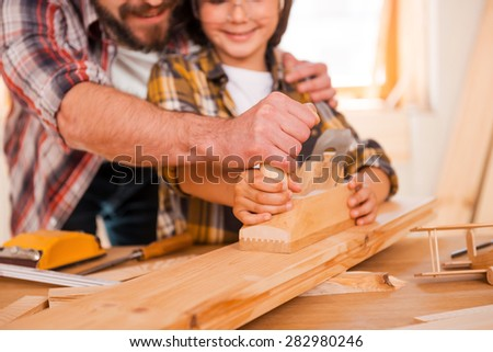 Sharing skills with his son. Close-up of smiling young male carpenter teaching his son to work with wood in his workshop - stock photo