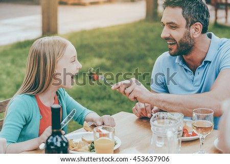 Sharing the best pieces. Happy young man feeding his daughter with salad while sitting together at the dining table outdoors - stock photo