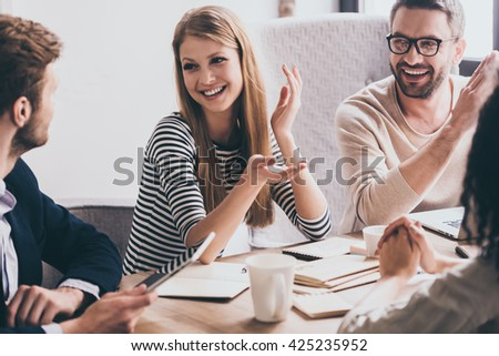 Sharing the latest news. Cheerful young people looking at each other with smile while sitting at the office table at the business meeting - stock photo