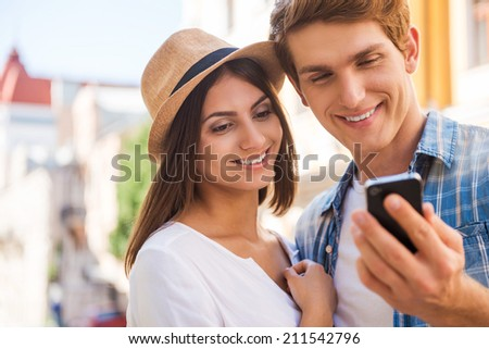 Sharing their pictures with friends. Beautiful young loving couple standing close to each other while man holding mobile phone and smiling  - stock photo