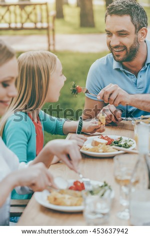 Sharing with the nearest. Happy young man feeding his daughter with salad while sitting together at the dining table outdoors - stock photo