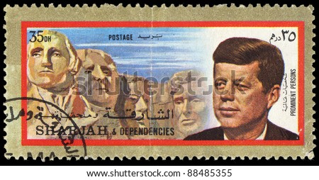 SHARJAH - CIRCA 1973: A stamp printed in Sharjan shows 35th president of USA John Fitzgerald Kennedy against statue of Mount Rushmore National Memorial, circa 1973. - stock photo