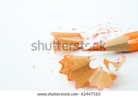 sharp orange pencil and shavings isolated on white background. Macro with extremely shallow depth of field - stock photo