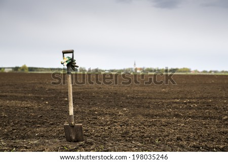 Sharp shovel with glowes on cultivated farm field - stock photo