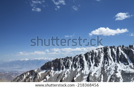 Sharp snow covered mountain ridge with high mountain range background - stock photo