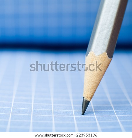 Sharp wooden pencil on blue checkered paper - stock photo