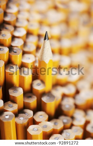 Sharpened pencil amongst the non-sharpened ones. Very short depth-of-field. - stock photo